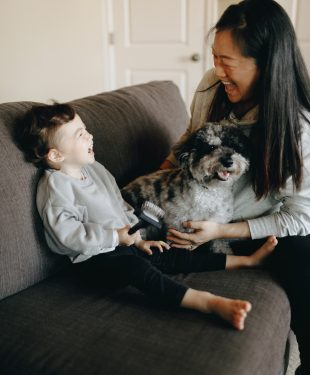 Happy mother and child sitting on sofa with their pet dog