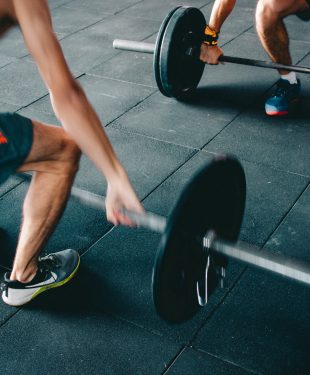 Man wearing black shorts lifting heavy barbells