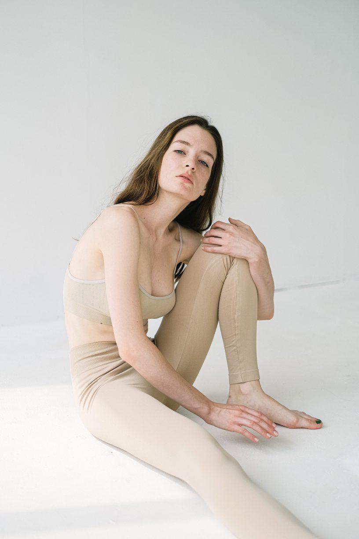 Slim woman sitting on floor in studio