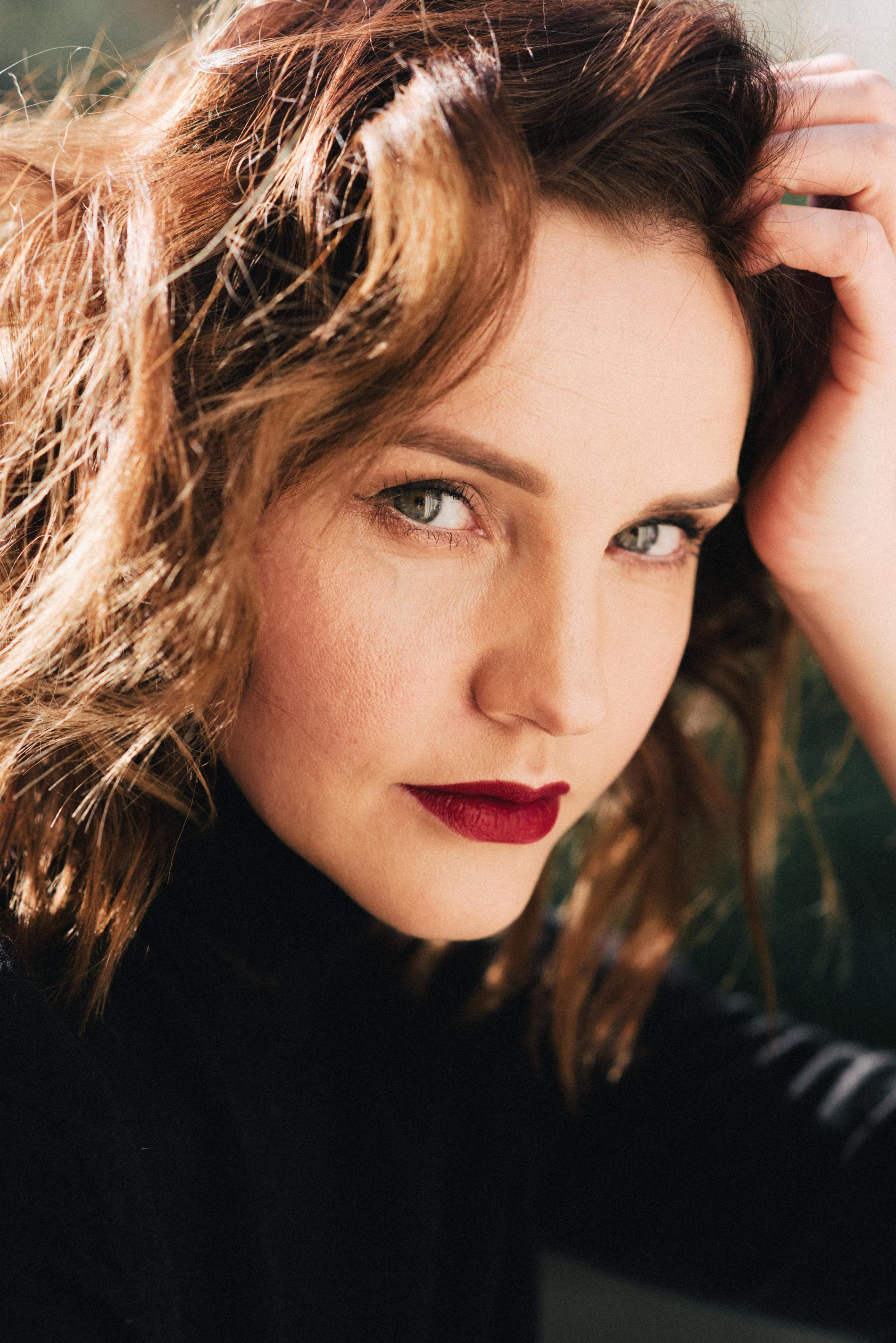 Woman with red lips and wavy hair in sunshine