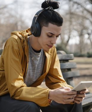 Young man with earphones and tablet on street
