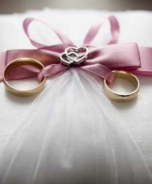 Selective focus photography of silver colored engagement ring set with pink bow accent on throw pillow