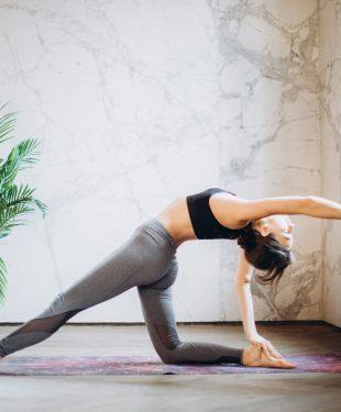 Woman in gray leggings and black sports bra doing yoga on yoga mat