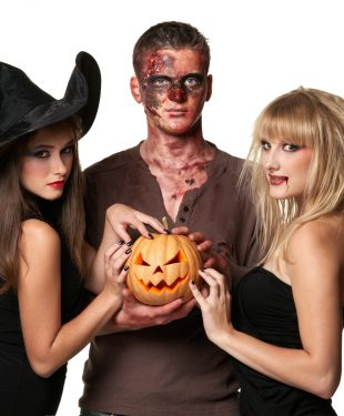 vampire, zombie and witch holding a pumpkin