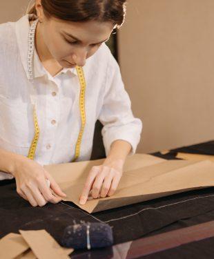 Woman putting a pattern on a black fabric